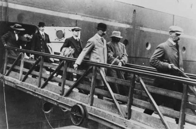 A handcuffed Crippen is led ashore