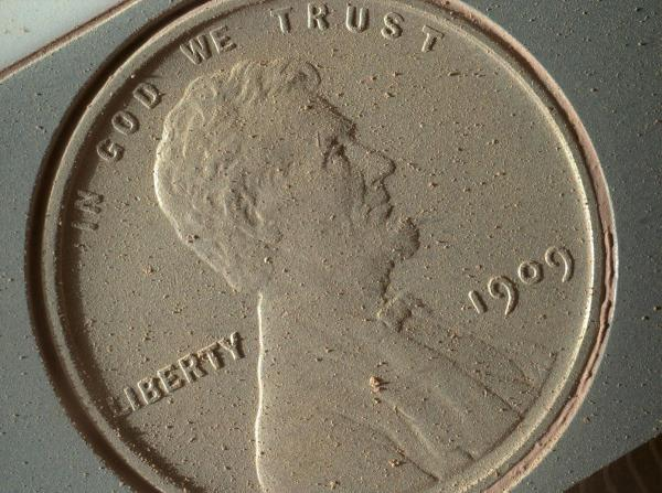 1909 penny being carried by the Mars Curiosity rover is caked with dust on Oct. 2, 2013, after 14 months on Mars. Credit: NASA/JPL-Caltech/MSSS/Planetary Science Institute